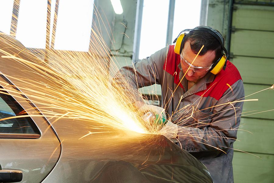 mechanic grinding car body