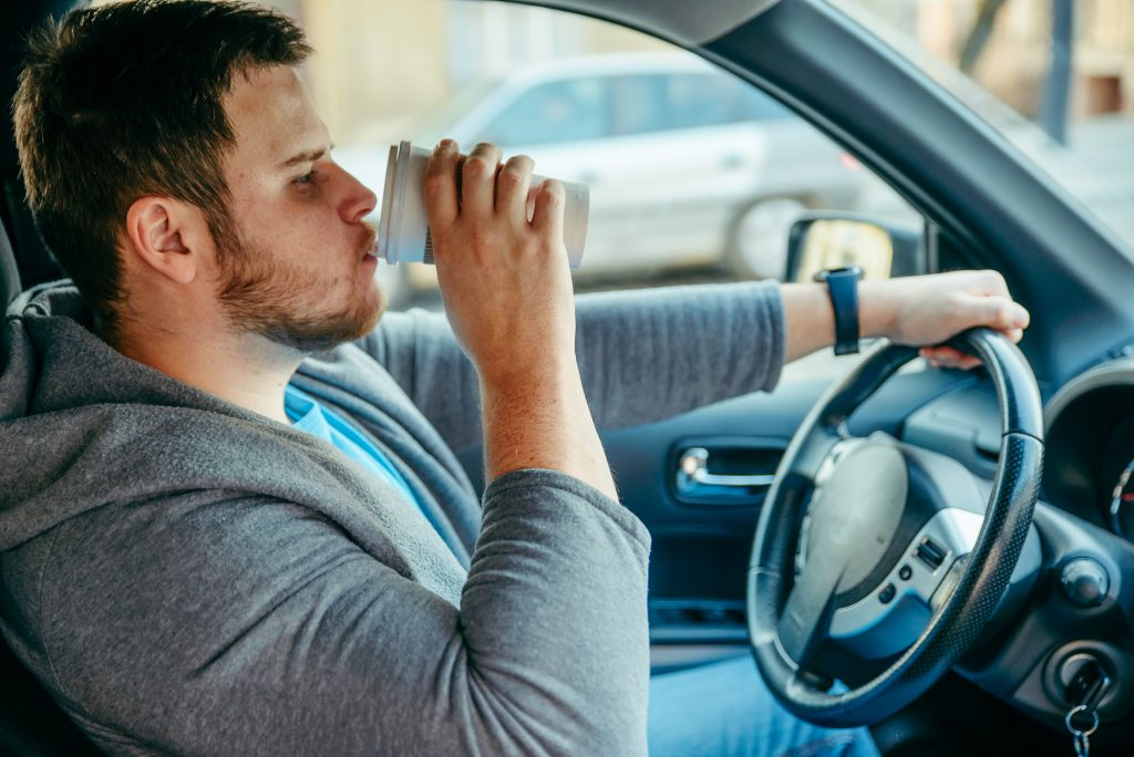 Man Driving Car And Drinking Coffee
