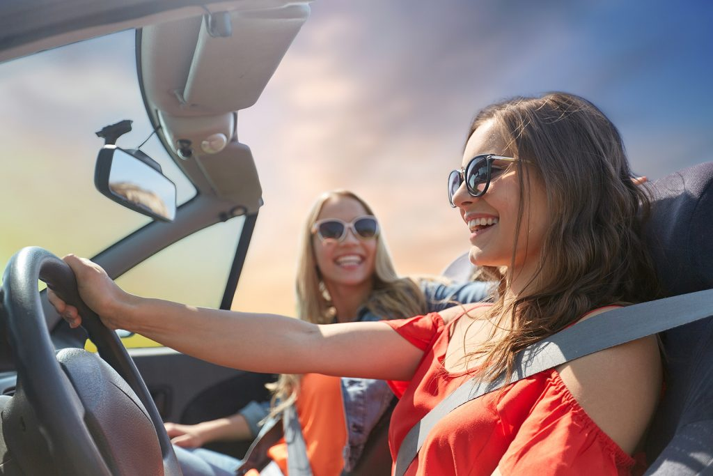happy young women driving in car