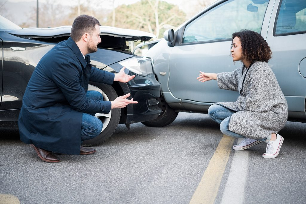 Man and young woman arguing after car accident