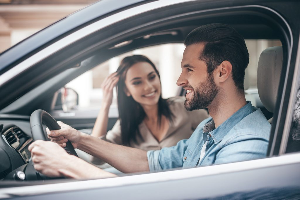 Beautiful young couple driving a car
